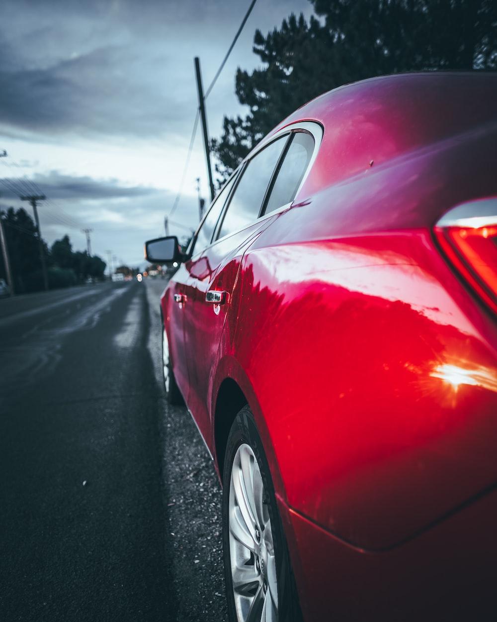 red sedan on road near utility pole