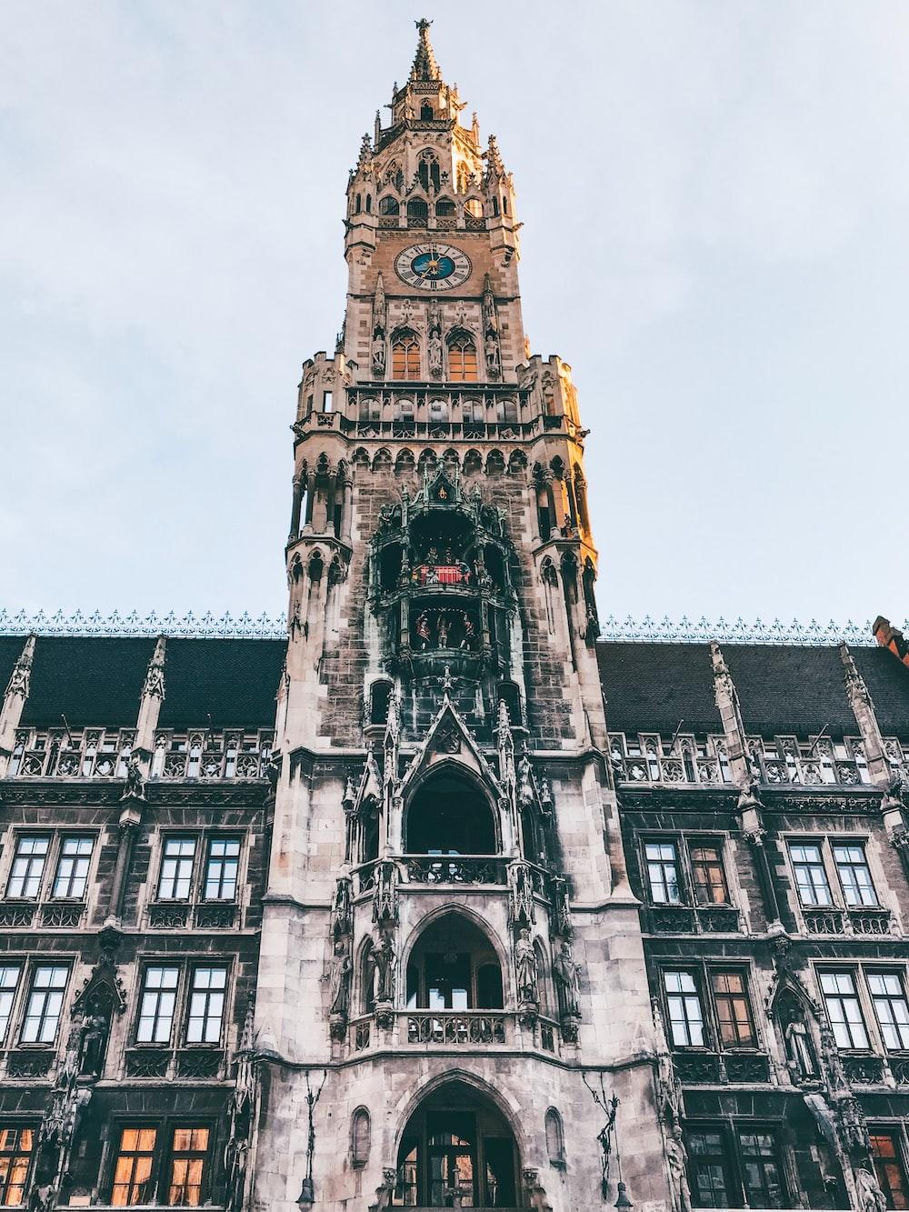 beige tower clock under white clouds