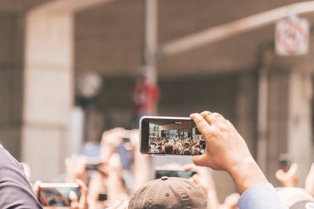 selective focus photography of person holding smartphone taking video