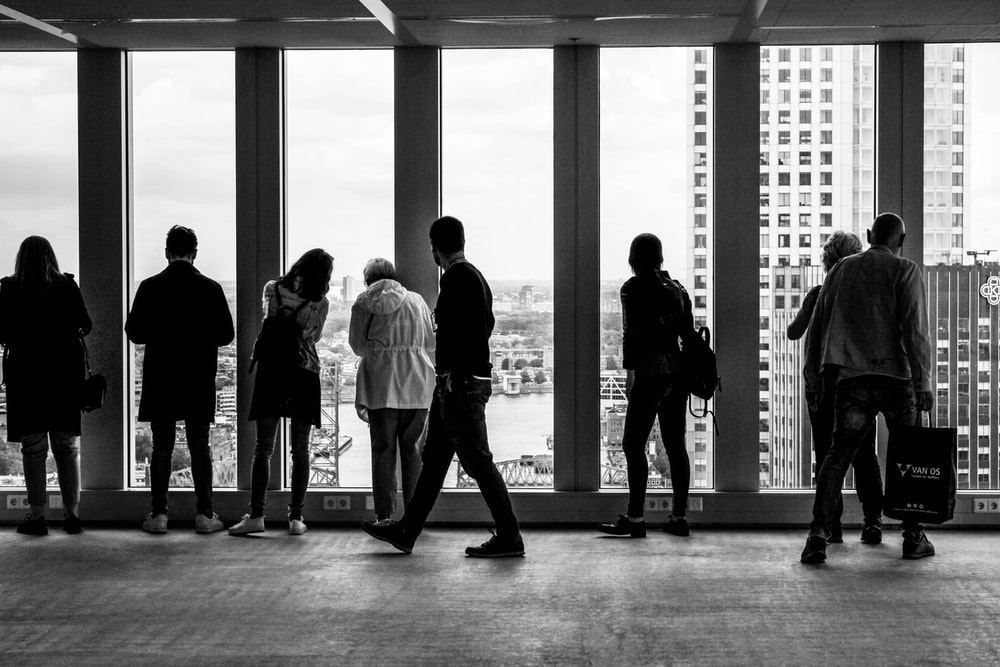 people standing in building grayscale photography