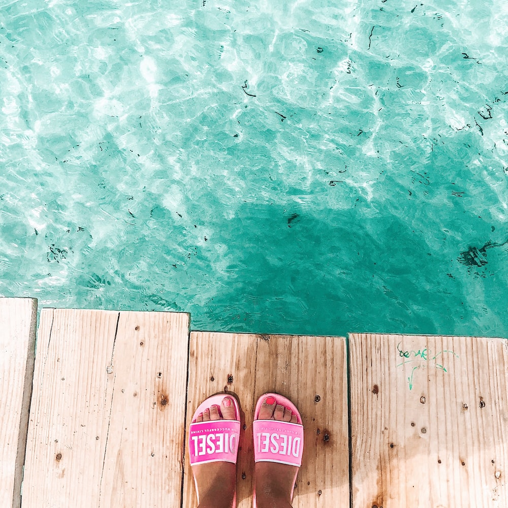 woman wears pink slide slippers standing on dock in front clear water