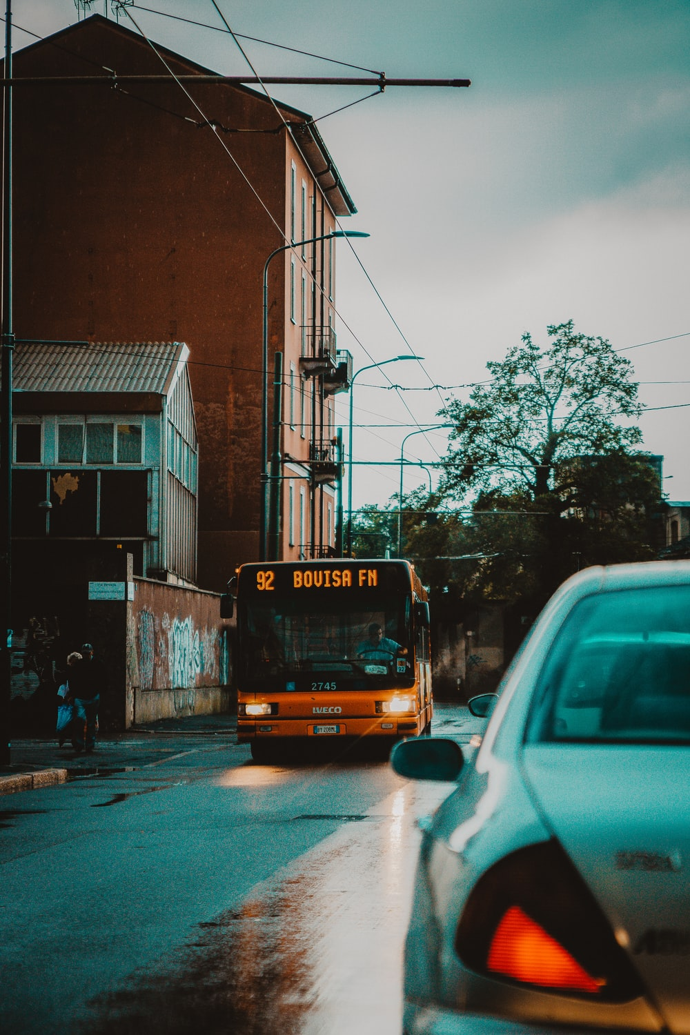 orange bus in road during daytime close-up photography