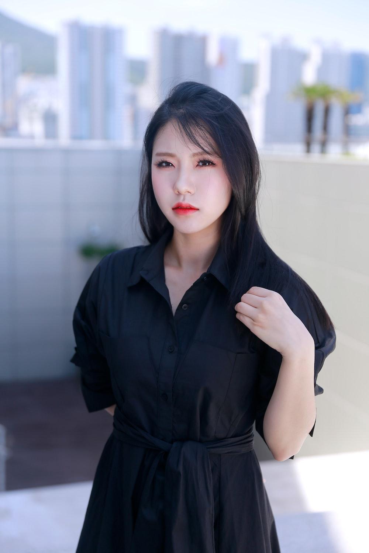 woman wears black collar wrap dress