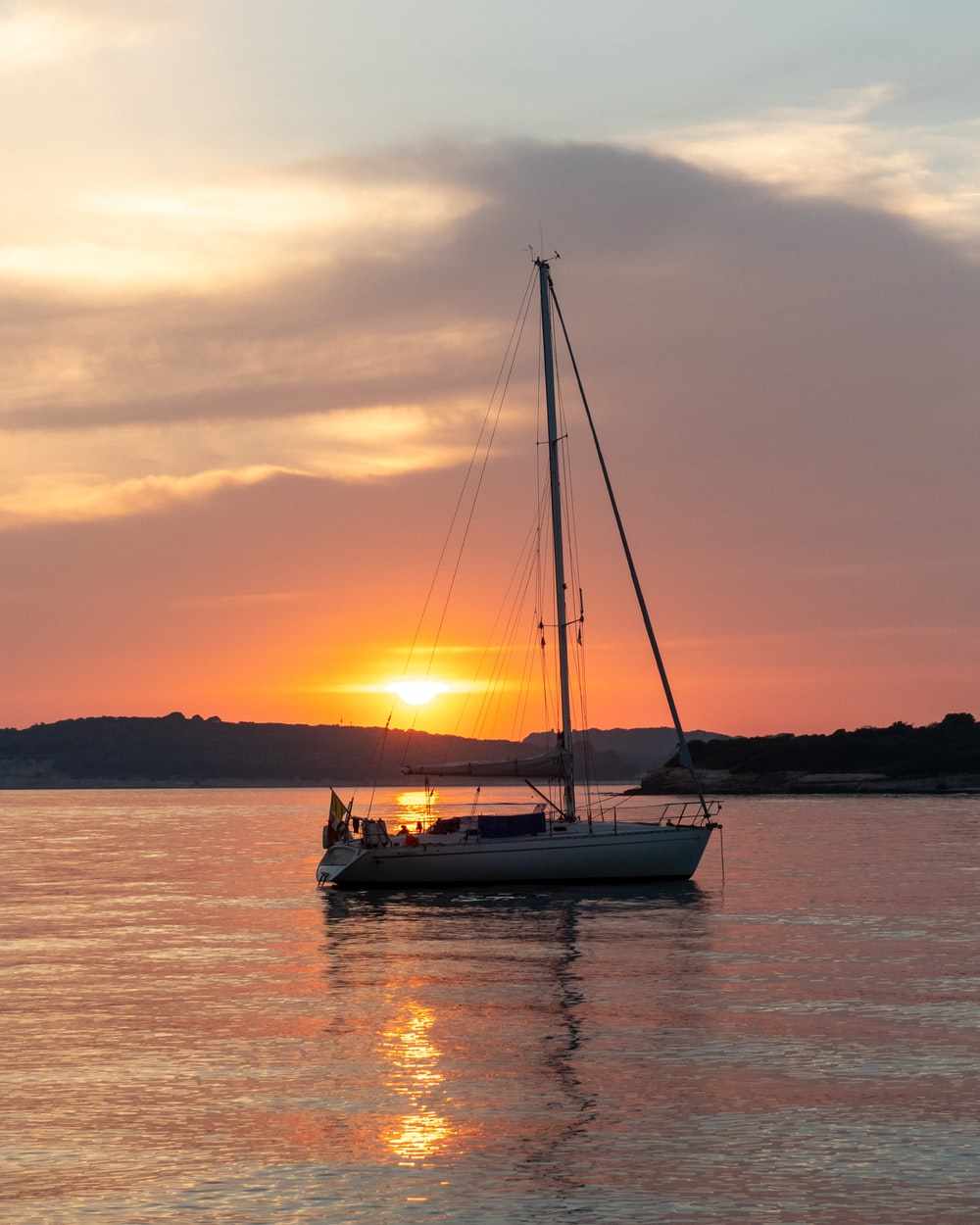 white sail boat on body of water during sunset