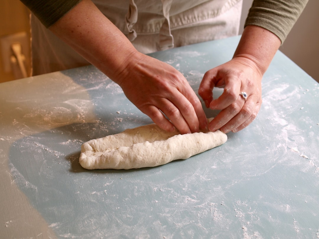 A woman forms dough into a loaf. She'll bake it and it'll be a French baguette.
