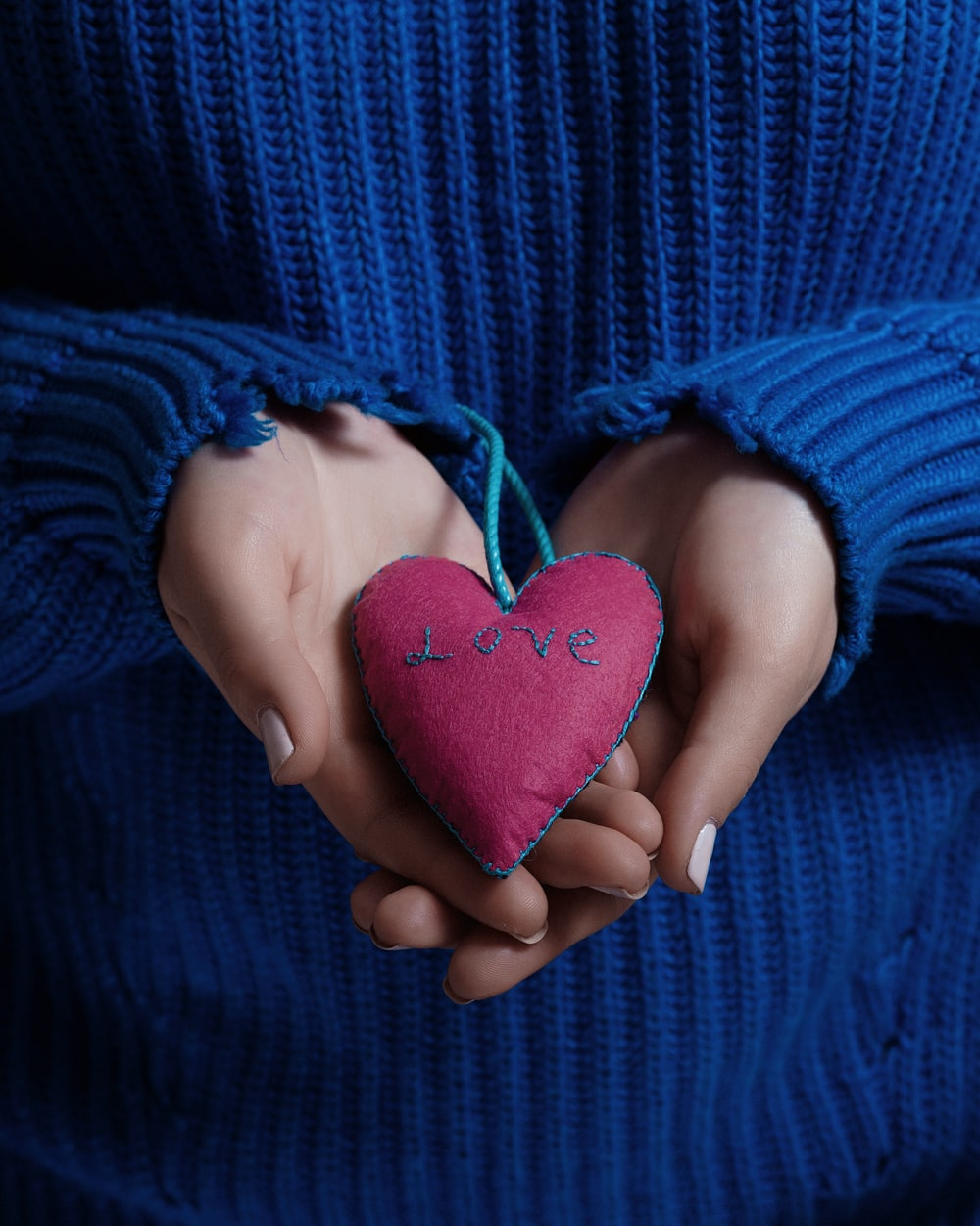 person holding heart-shaped red cushion