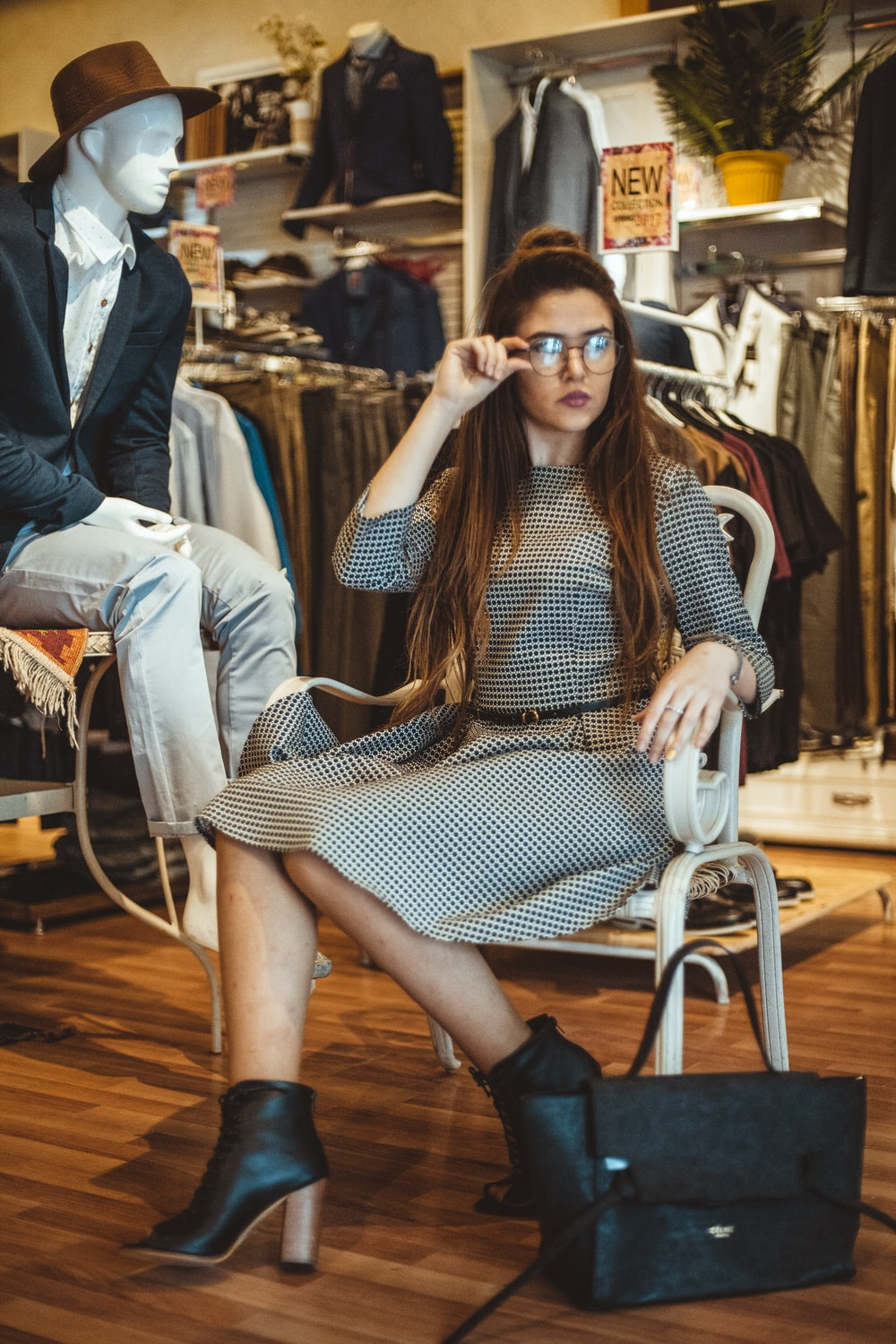 woman sitting on chair while holding her glasses