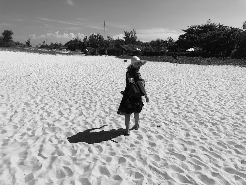women wearing a summer hat in a sandy land grey-scale photography