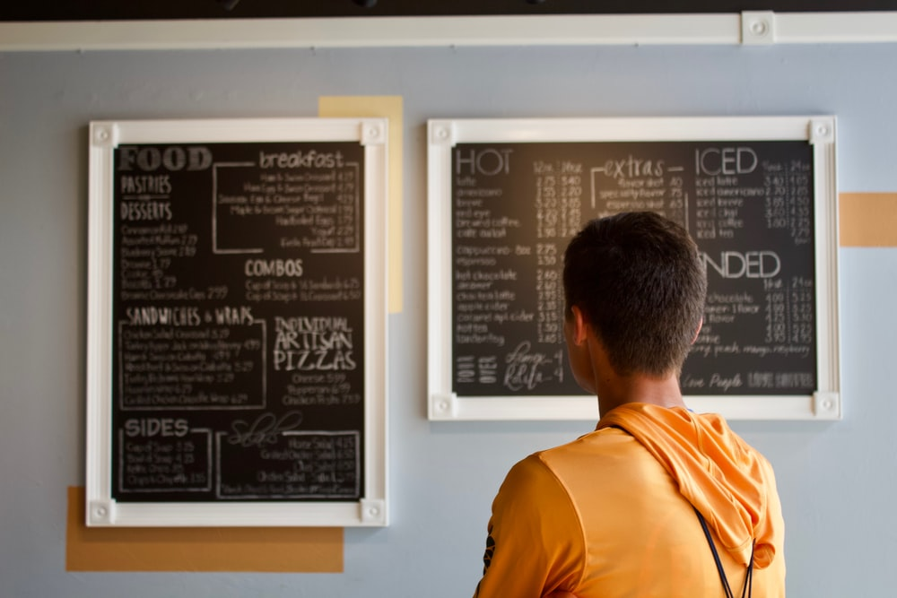 man standing beside menu