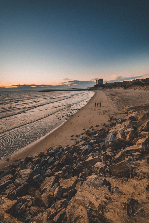three persons walking beside beach line