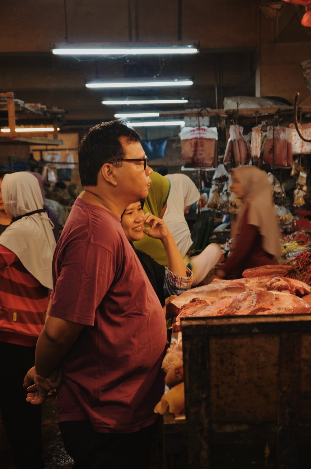 man standing in front of meat shop