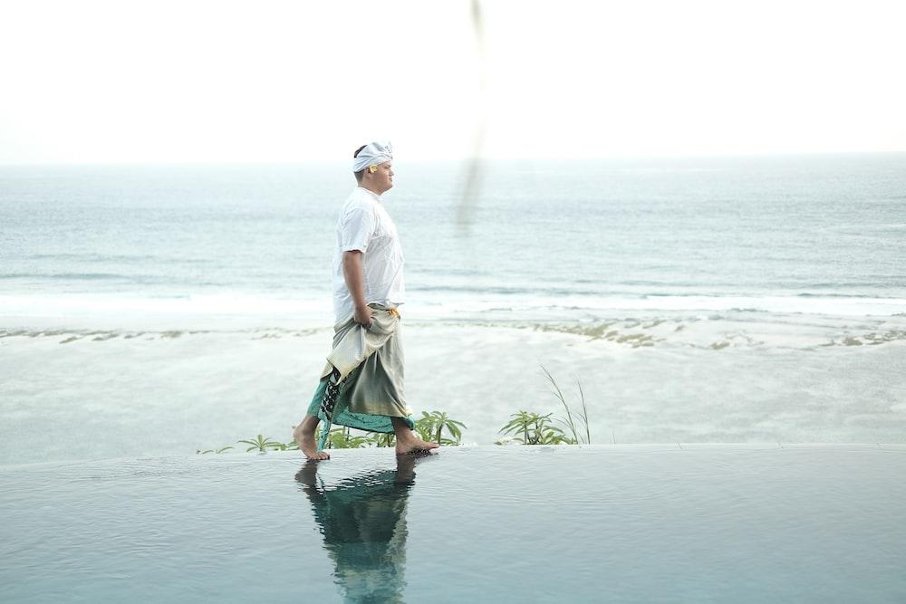 man walking on seashore during daytime