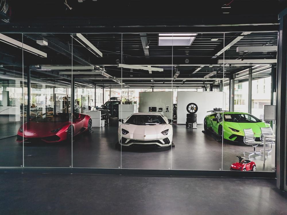three white, red, and green Lamborghini coupes