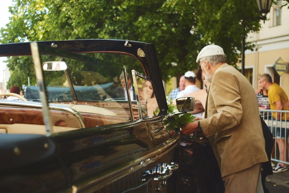 man in brown suit standing beside car