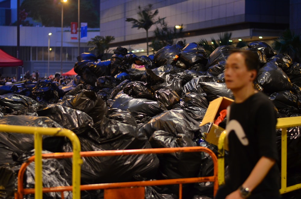 man in black shirt standing beside garbages