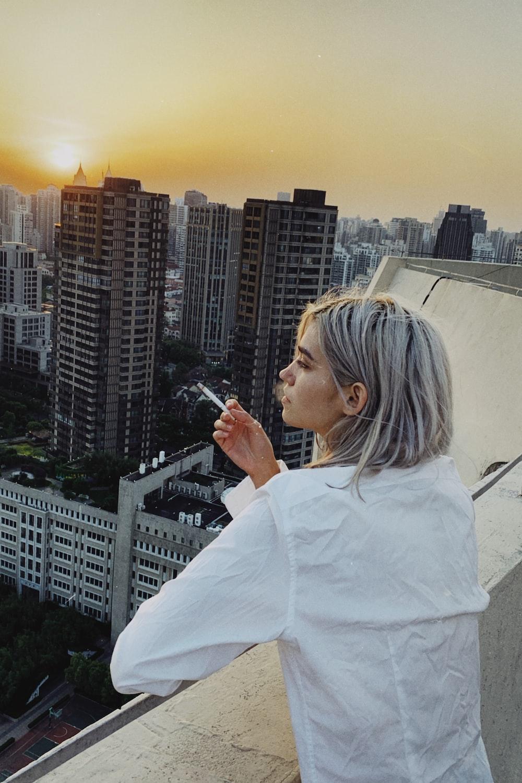 woman wearing white dress shirt smoking