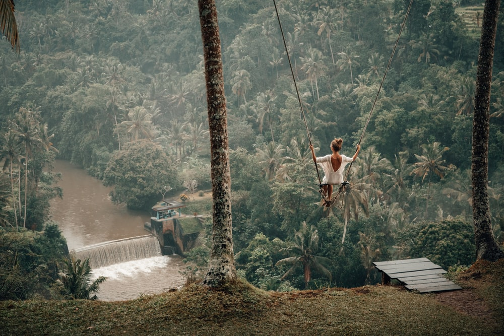 woman wearing white top on swing across river