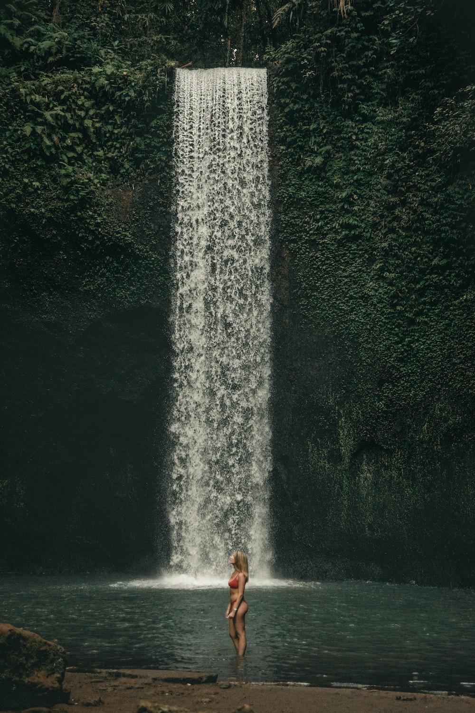 woman standing near waterfall during daytime