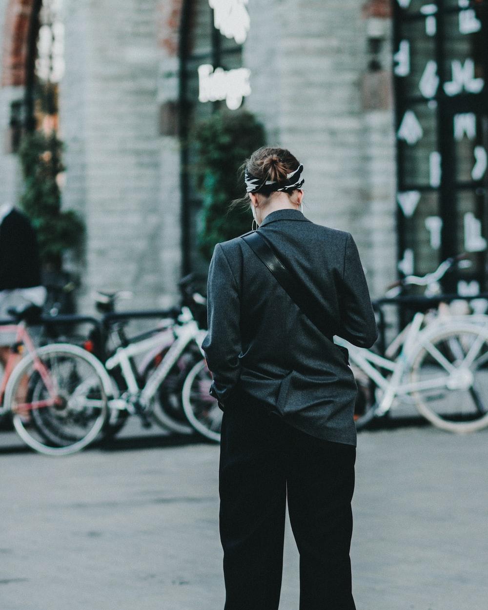 woman wearing black jacket walking on street