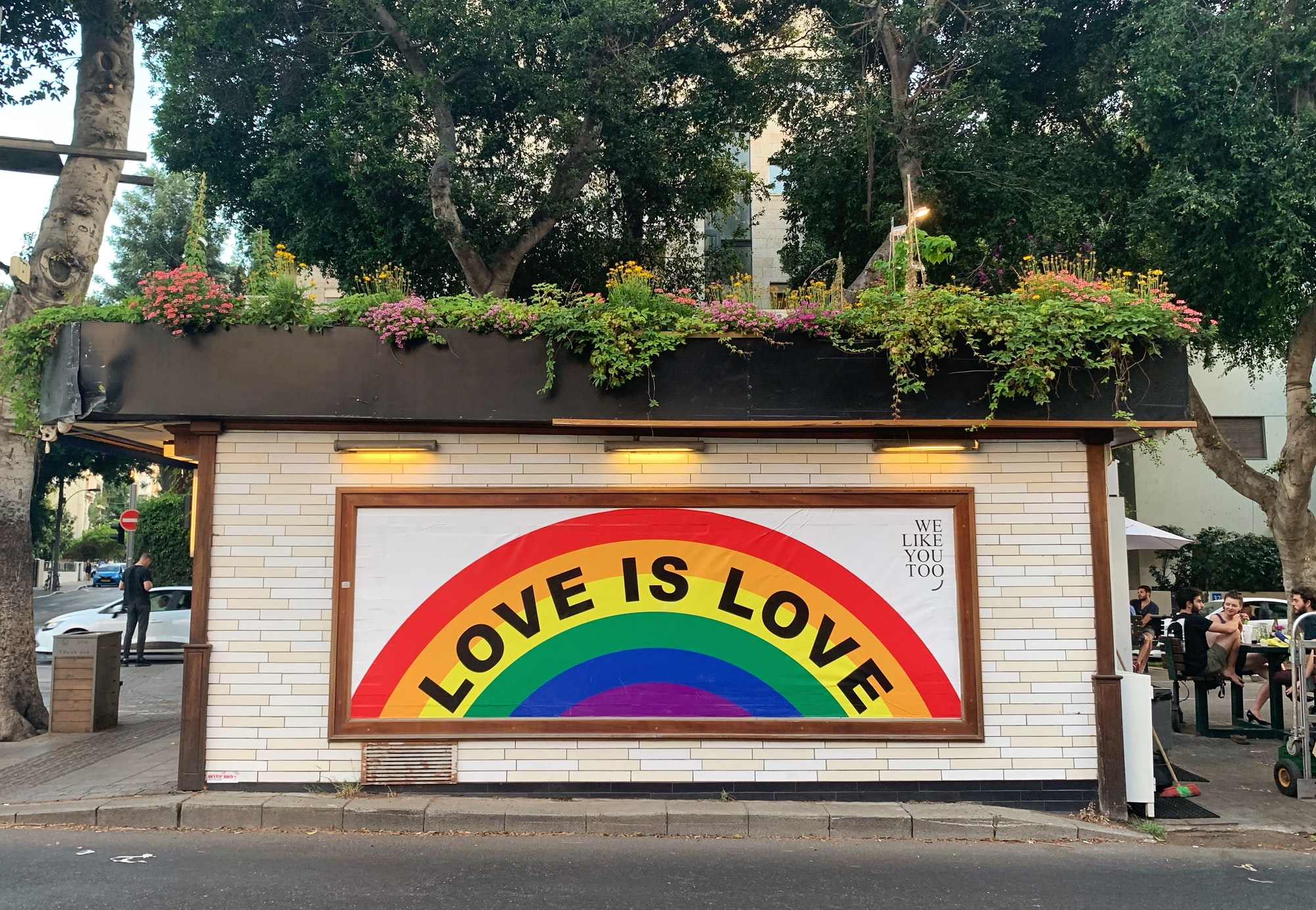 """Rainbow with the words """"love is love"""" painted across it."""