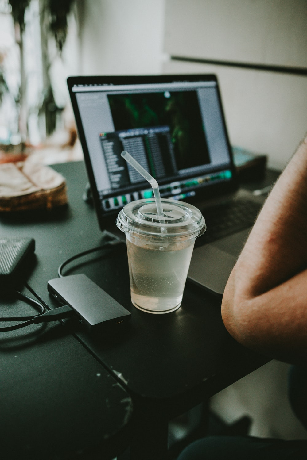 person using laptop while drinking liquid