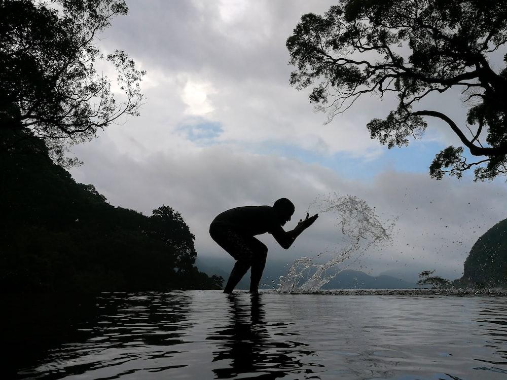 silhouette of person splashing water