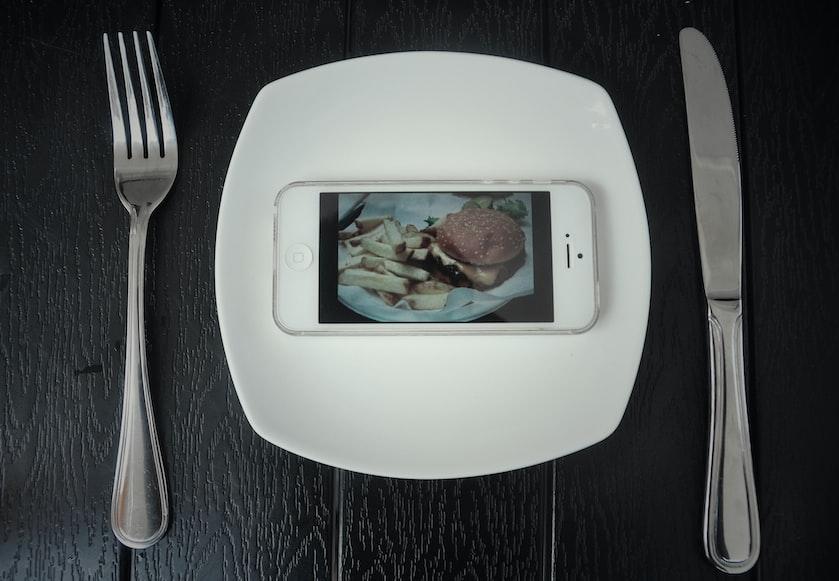 piatto con un cellulare che mostra l'immagine del cibo