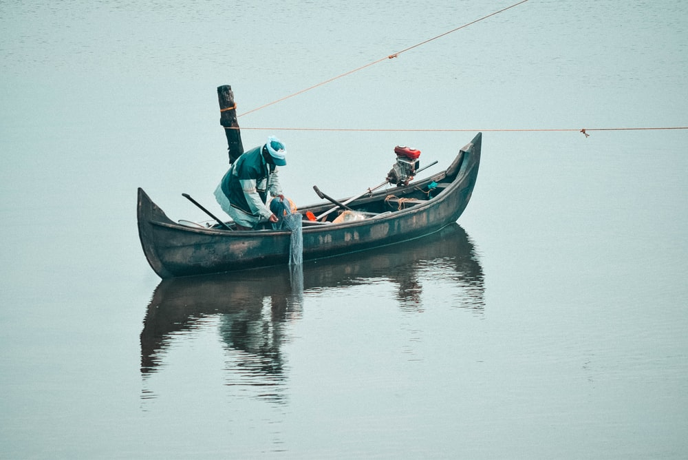person on boat holding fishing net