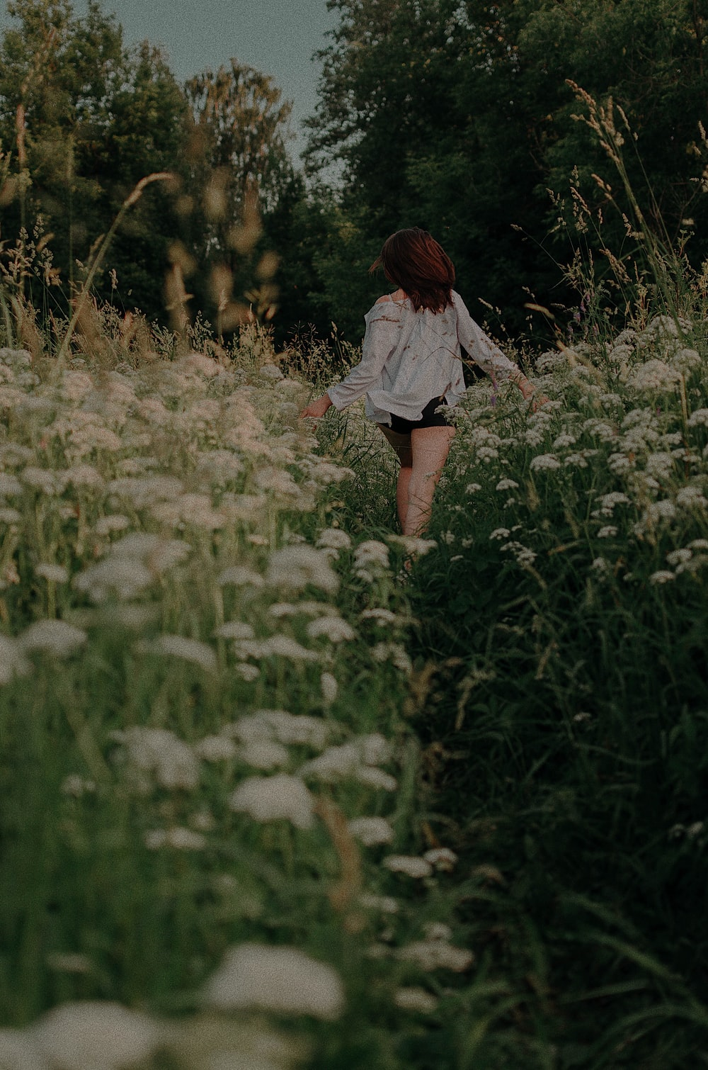 girl running in white flower field during daytime