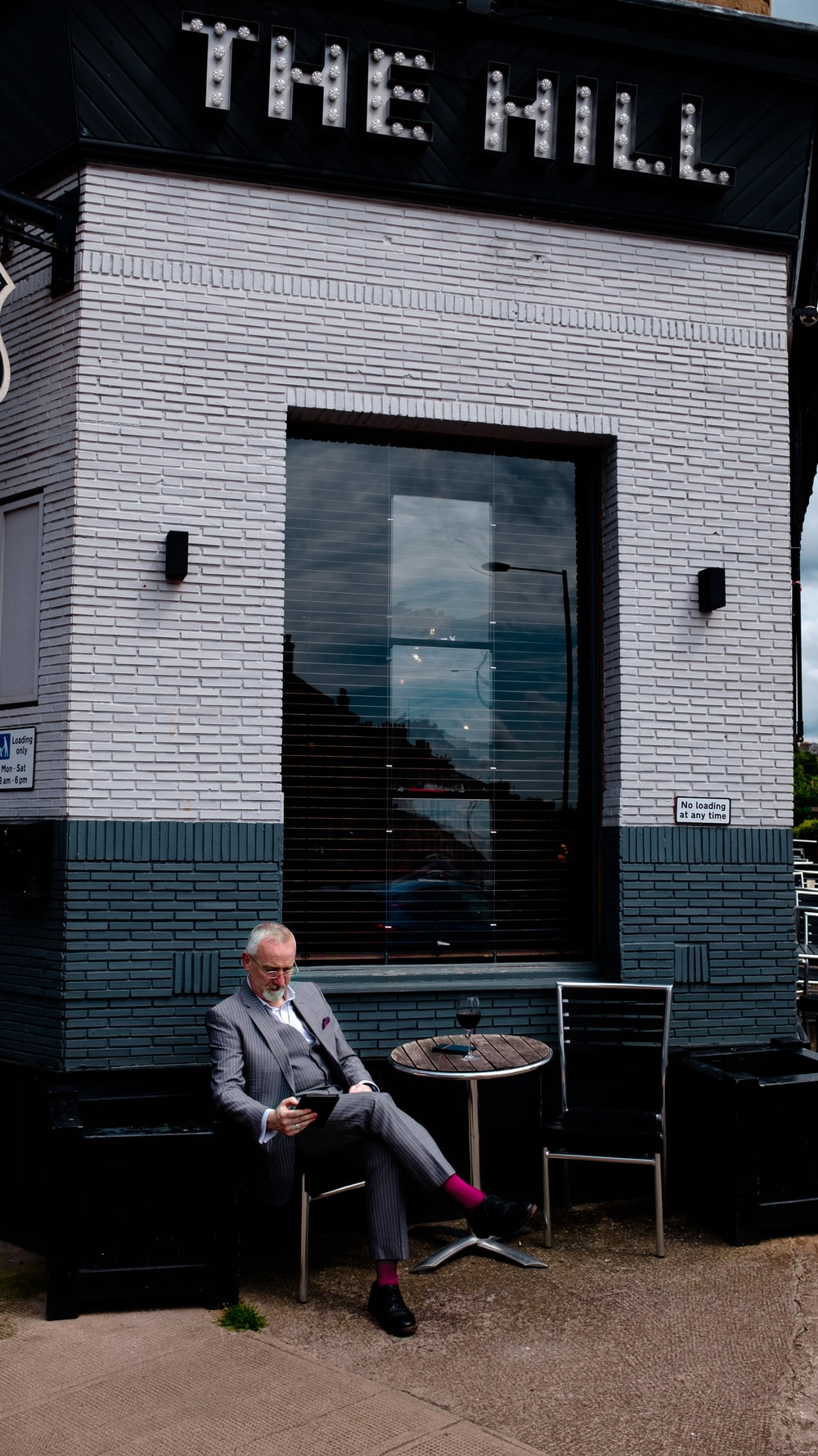man in grey suit sitting on chair beside table in front of The Hill building