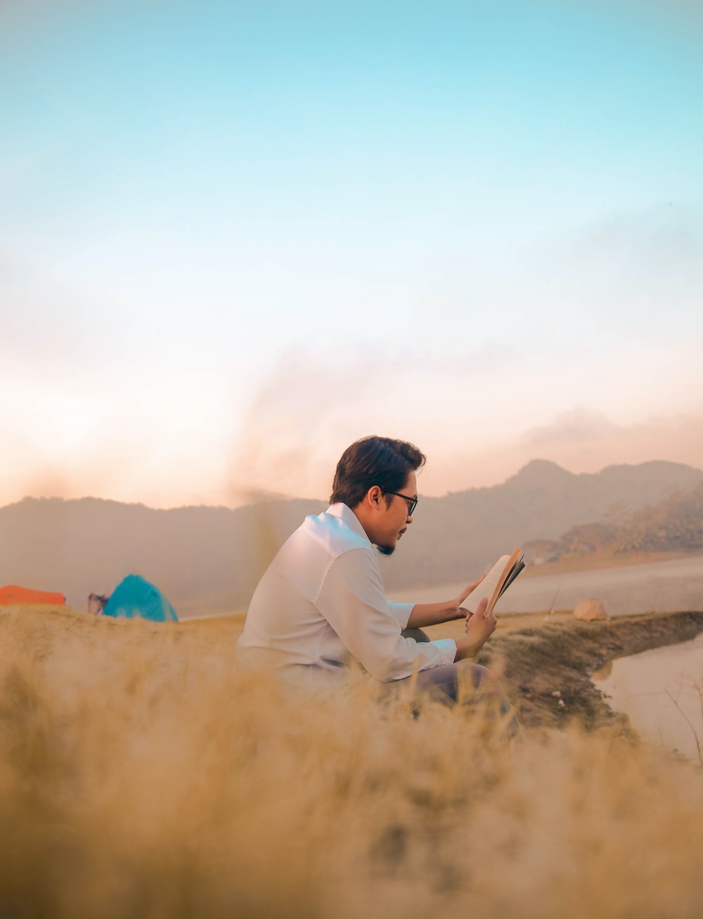 man reading book on a mountain top