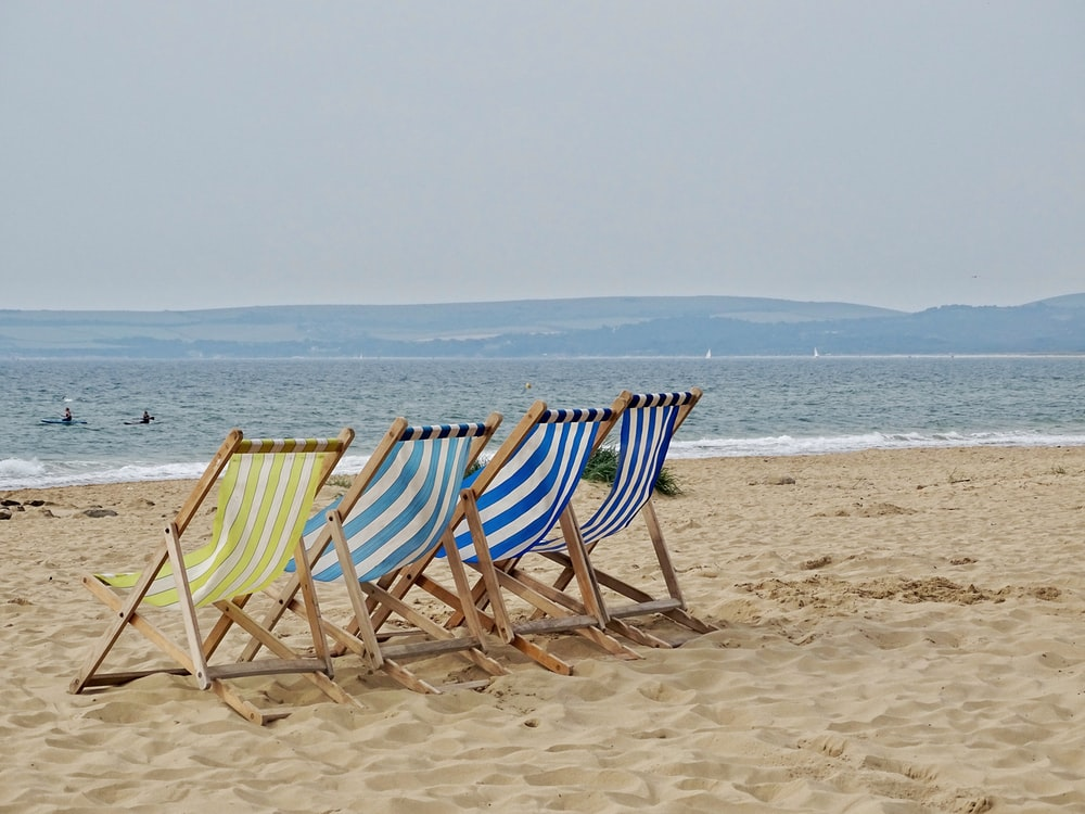 lined four chairs in front of beach