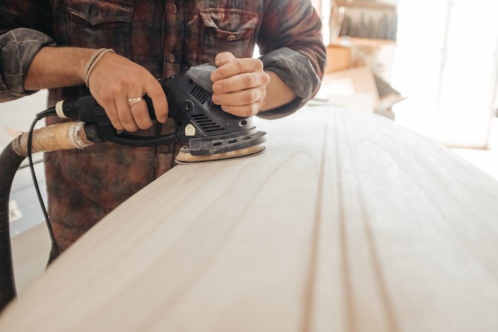 man using sander on beige wooden surface