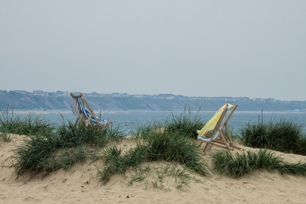 two yellow and brown loungers on shore