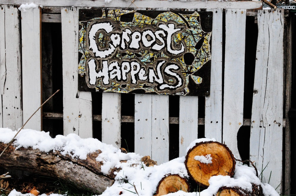 snow covered log beside wooden wall with sign