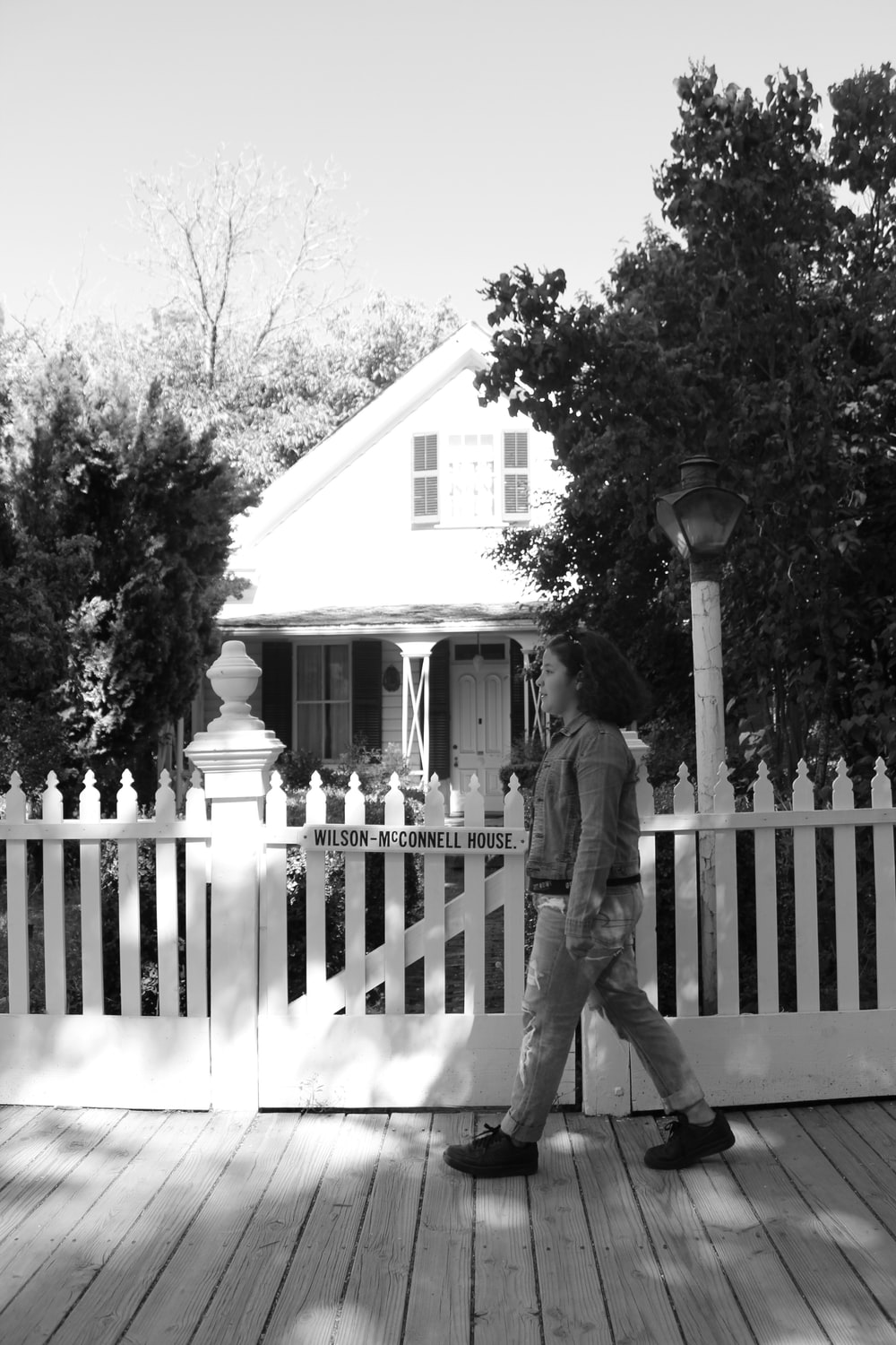 grayscale photo of woman walking beside fence