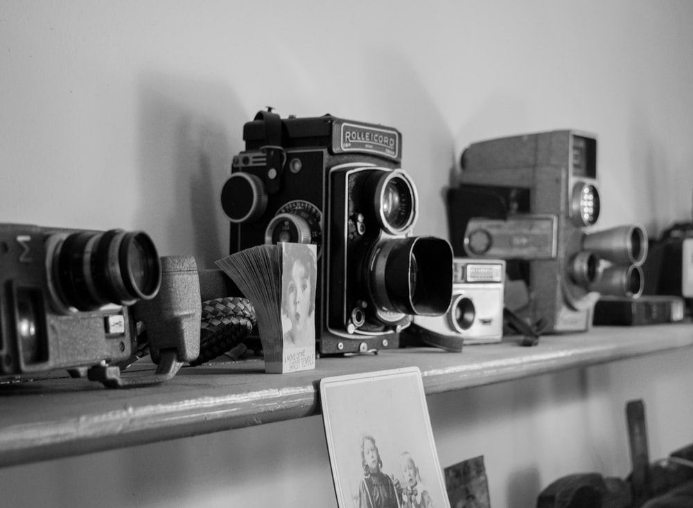 grayscale photo of several cameras on shelf