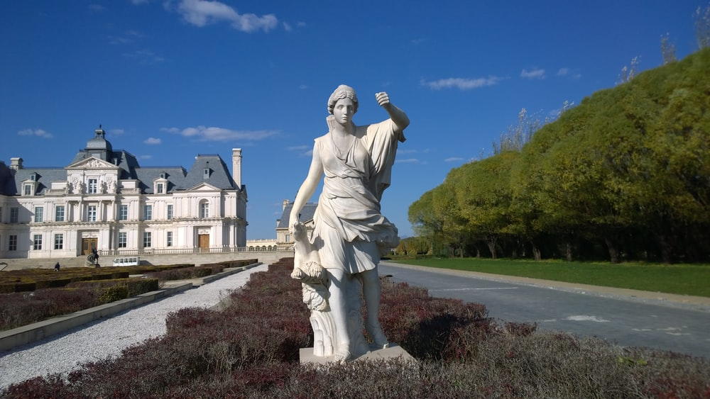 white statue of woman besides road