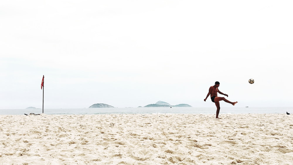 man playing soccer on beach