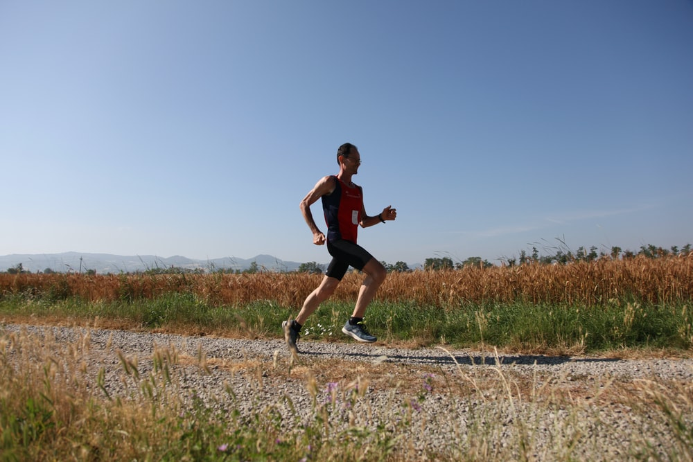 man red and black top running on farm road