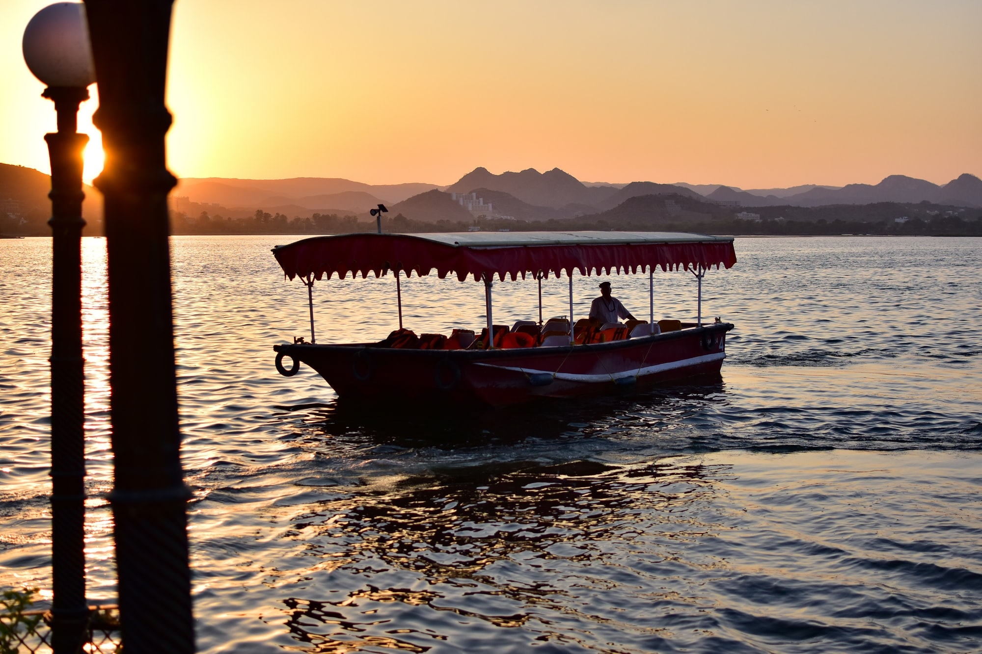 A beautiful sunset on the lake pichola at Udaipur as the boat approaches to pick us up. A must visit! Udaiur, travel, india, sunset