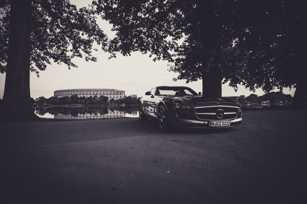grayscale photography of car parked near tree