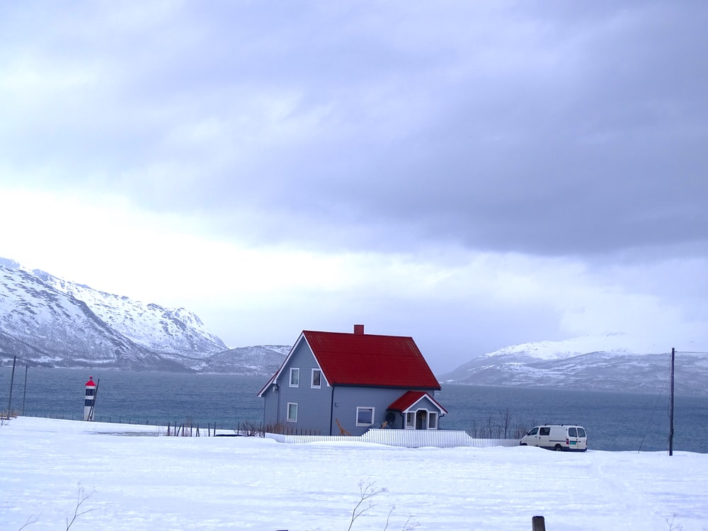 gray and red house near body of water and mountains