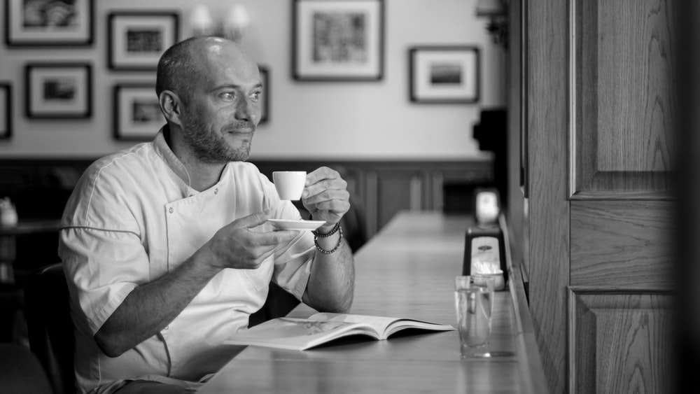 grayscale photo of man holding cup and saucer