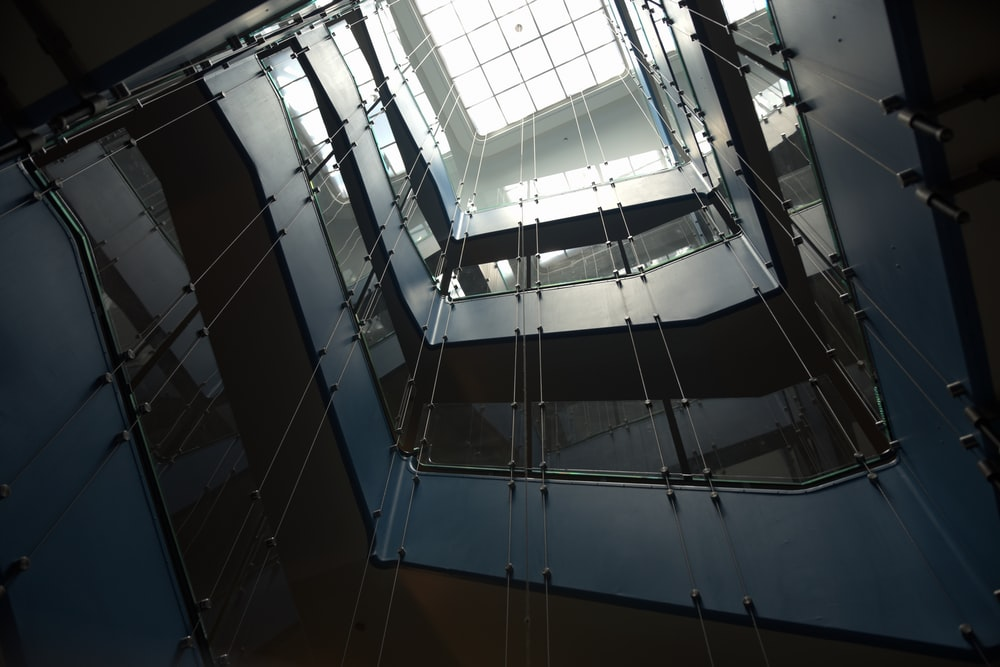 low-angle photography of multi-storey building with glass ceiling
