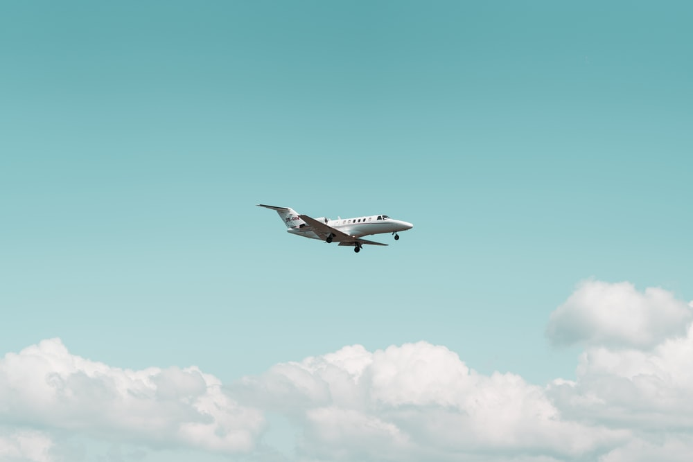 white airplane flying under Cumulus clouds