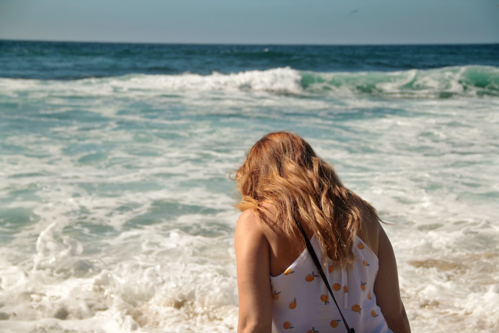 woman wearing white and yellow tank top standing near blue sea during daytime