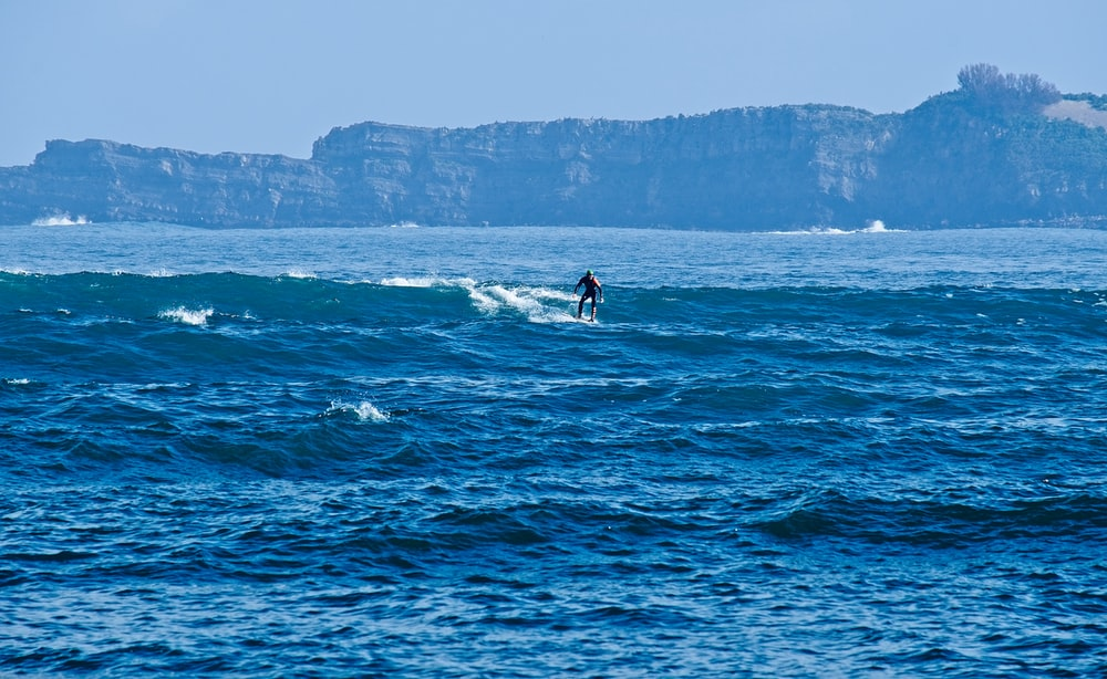 man surfing at the ocean during day