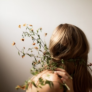 blonde woman holding green and yellow petaled flowers
