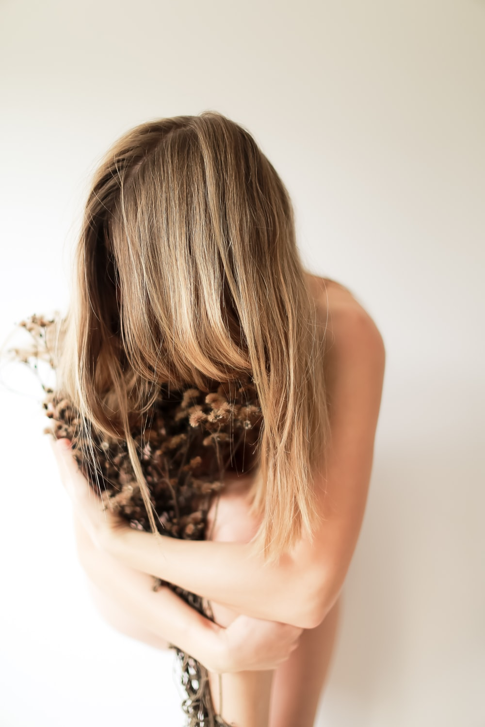 naked woman hugging dried plant